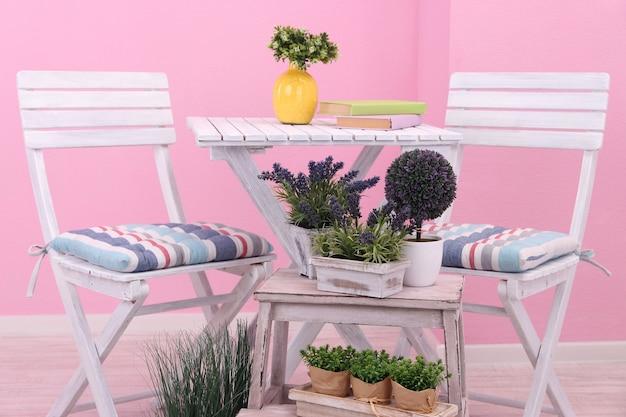 Cadeiras de jardim e mesa com flores em suporte de madeira rosa