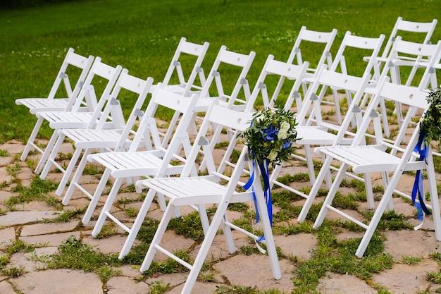 Cadeiras de madeira brancas decoradas com flores e fitas de cetim brilhantes, decoração de casamento na cerimônia.