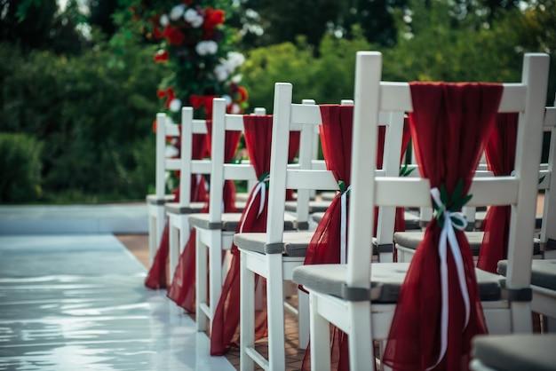 Cadeiras de madeira brancas decoradas com tecido vermelho e fitas para recepção de casamento ao ar livre