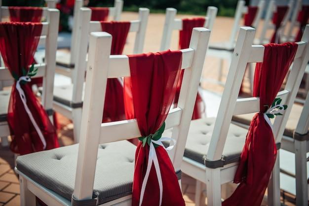 Cadeiras de madeira brancas decoradas com tecido vermelho e fitas para registro de casamento ao ar livre