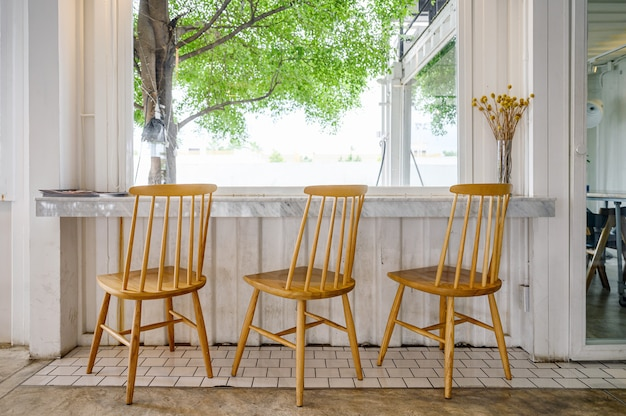 Cadeiras de madeira com barra de mármore e árvore do lado de fora