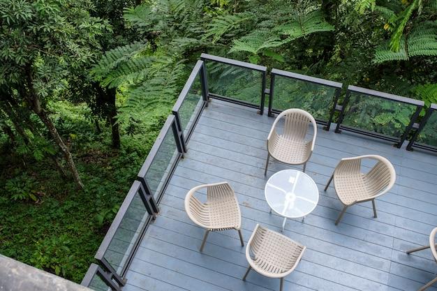 Cadeiras de madeira com mesa de vidro no pátio no jardim