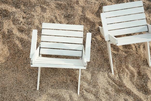 Cadeiras de madeira em uma praia arenosa.