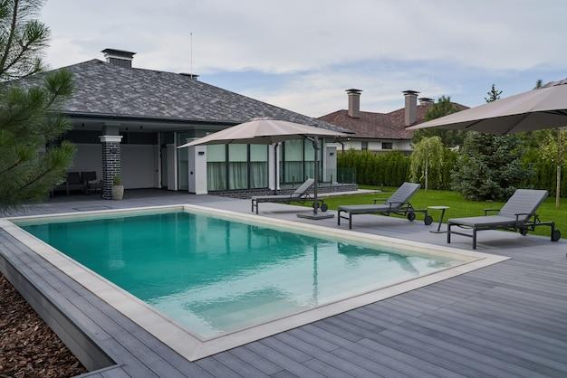 Cadeiras de madeira na piscina e deck da villa moderna. piscina de água azul clara de uma luxuosa mansão com cadeiras ao redor. casa moderna ao fundo