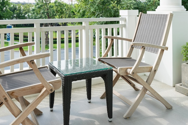 Cadeiras de madeira na varanda moderna com vista para um jardim