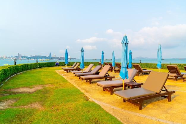 Cadeiras de piscina e guarda-sol ao redor da piscina
