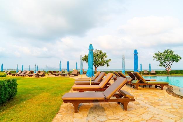Cadeiras de piscina ou piscina e guarda-sol ao redor da piscina com praia de mar