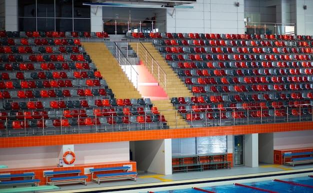Cadeiras de plástico em arquibancada vazias em uma grande piscina esportiva para natação e mergulho