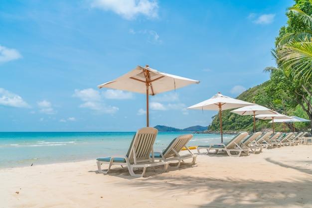 Cadeiras de praia bonitas com guarda-chuva na pra areia branca tropical