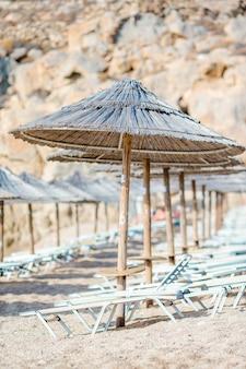 Cadeiras de praia de madeira e guarda-chuvas para férias na praia na grécia