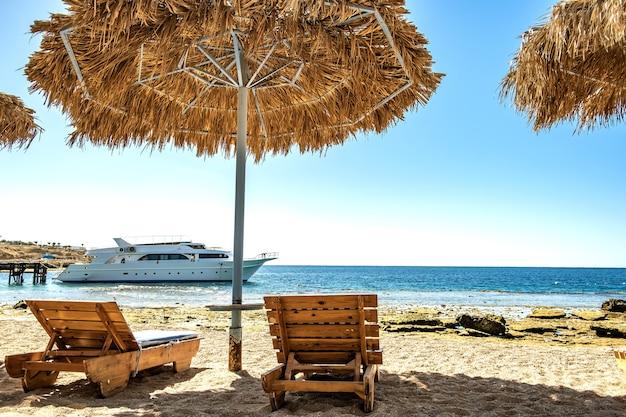 Cadeiras de praia de madeira sob o guarda-sol de palha áspera na praia do mar e o grande iate branco na água perto da costa num dia ensolarado de verão.