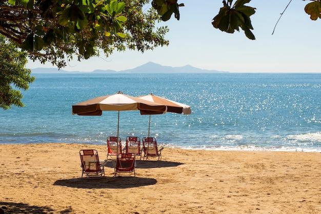 Cadeiras de praia e guarda-chuva na areia com bela vista. oceano azul.