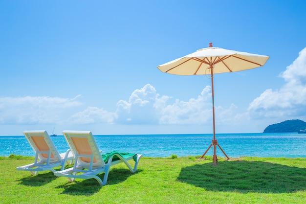 Cadeiras de praia e guarda-sóis estão no gramado na praia.