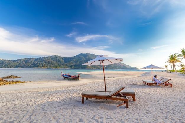 Cadeiras de praia, guarda-chuva e palmas das mãos na bela praia para férias e relaxamento na ilha de koh lipe, tailândia
