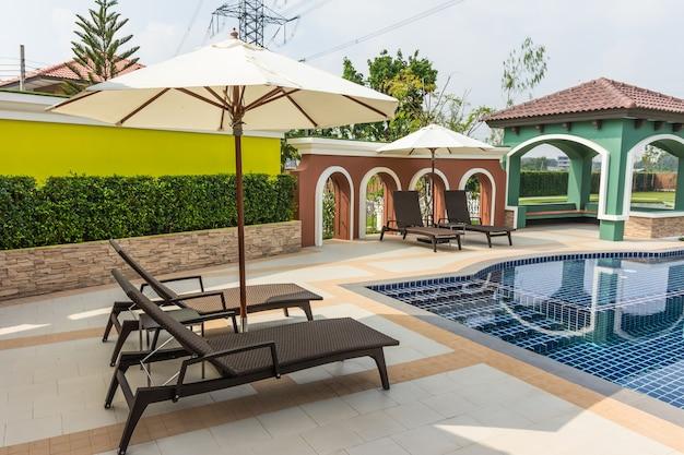 Cadeiras de praia lado piscina na tailândia