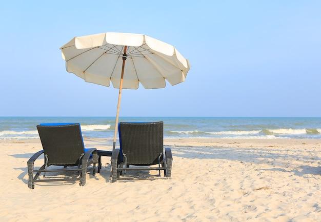 Cadeiras de praia na praia de areia com guarda-chuva branco no céu azul nublado e sol