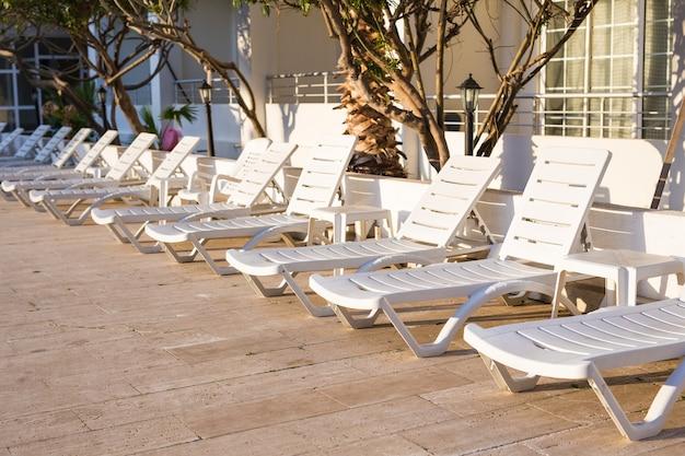Cadeiras de praia perto da piscina. espreguiçadeira na piscina convida você a relaxar