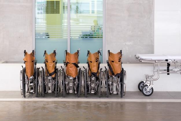 Cadeiras de rodas do hospital alinhadas com cama