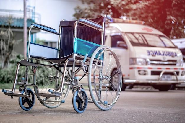 Cadeiras de rodas e ambulâncias estacionadas no hospital com luz vermelha.