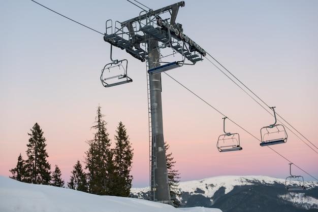 Cadeiras de teleférico na estância de inverno contra um lindo céu ao pôr do sol