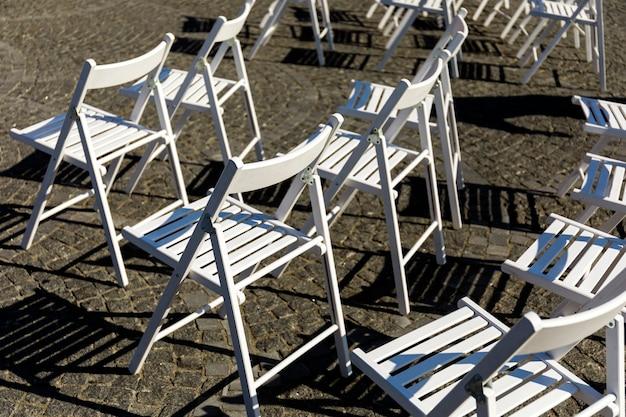 Cadeiras dobráveis brancas em um casamento ao ar livre