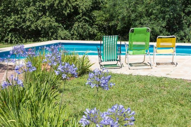 Cadeiras dobráveis perto da piscina e gramado no quintal