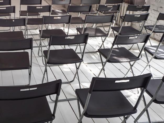 Cadeiras dobráveis pretas ficam em fila na sala de conferências branca