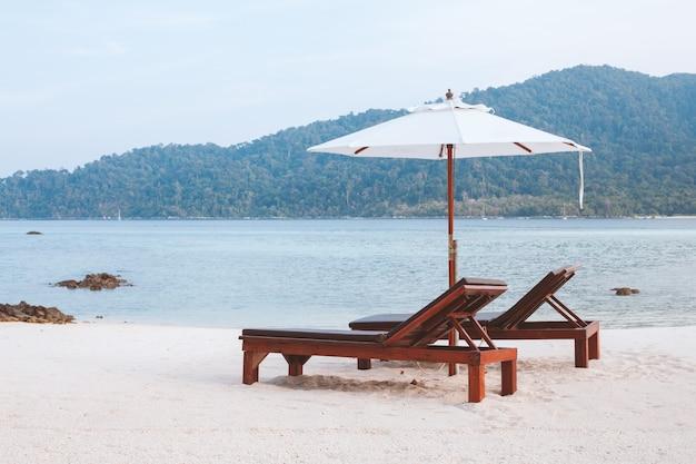 Cadeiras e guarda-chuva na praia de areia perto do mar