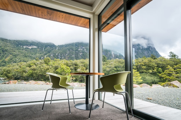 Cadeiras e mesa ao lado de uma grande janela com vista para a montanha
