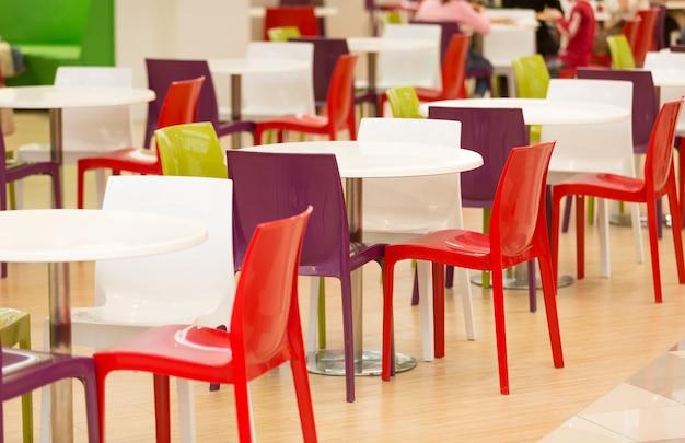 Cadeiras e mesas de plástico coloridas em grande cantina