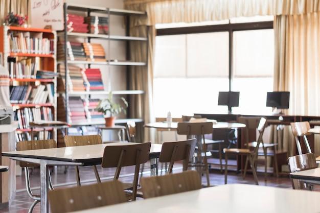 Cadeiras e mesas na sala de aula vazia