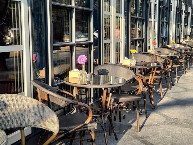 Cadeiras e mesas vazias do lado de fora, café urbano.
