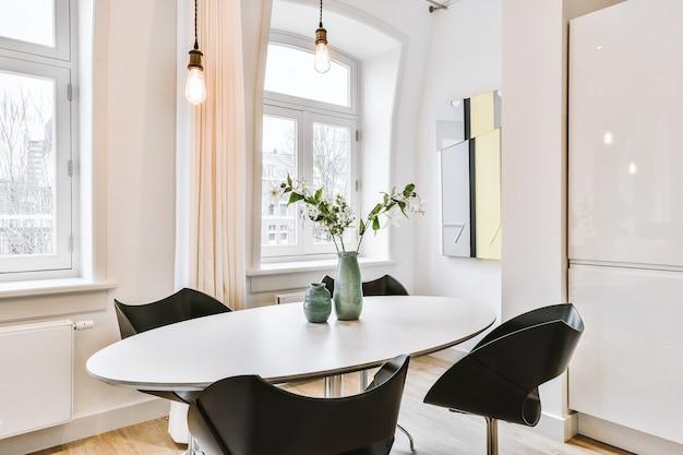 Cadeiras elegantes colocadas em torno de uma mesa oval com ramos floridos e vasos na sala de jantar iluminada em um apartamento moderno