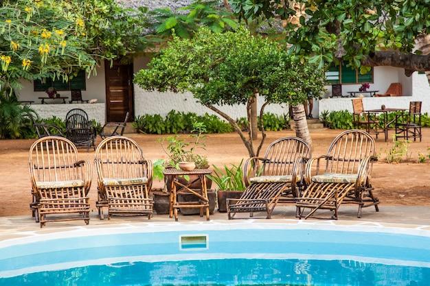 Cadeiras elegantes feitas de madeira perto de uma piscina dentro de um jardim queniano