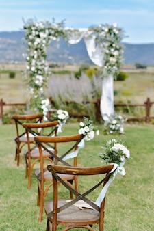 Cadeiras marrons chiavari decoradas com buquês de eustomas brancos na grama e o arco de casamento decorado no fundo no dia ensolarado