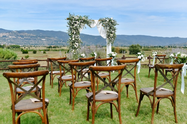 Cadeiras marrons chiavari e o arco de casamento decorado com flores brancas e vegetação no dia ensolarado
