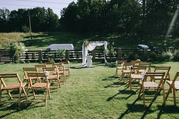 Cadeiras marrons ficar na frente de um altar weding em um gramado de grama