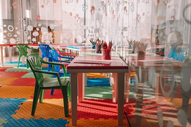 Cadeiras, mesa e brinquedos. interior do jardim de infância