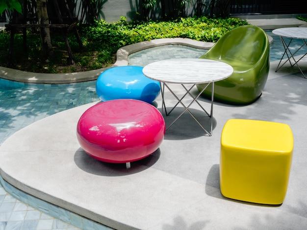 Cadeiras modernas de cores vivas e uma variedade de formas e mesa redonda ao lado da piscina externa.