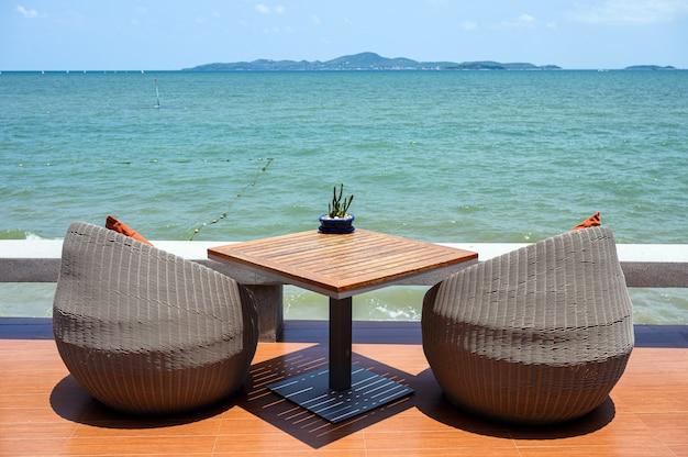 Cadeiras modernas do weave com a tabela de madeira com mar tropical
