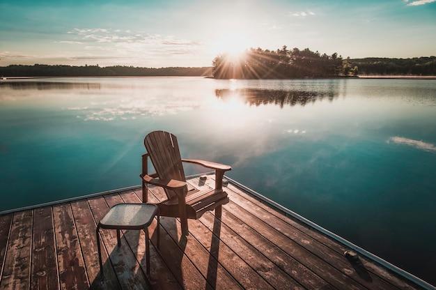 Cadeiras muskoka sentadas em uma doca de madeira de frente para um lago calmo. do outro lado da água está uma casa branca situada entre árvores verdes