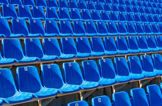 Cadeiras plásticas azuis dobradas em uma tribuna provisória,