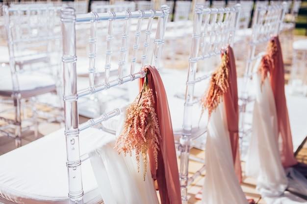 Cadeiras plásticas transparentes para cerimônia de casamento em uma fileira.