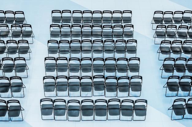 Cadeiras pretas colocadas na platéia, vista de cima.