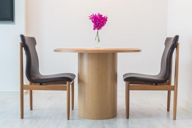 Cadeiras pretas com uma mesa de madeira