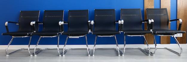 Cadeiras pretas em fila contra parede azul escritório moderno closeup. conceito de seminário de negócios