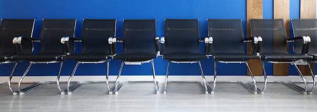 Cadeiras pretas na linha no escritório moderno de parede azul