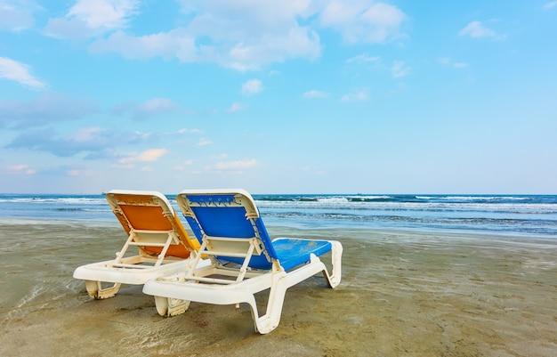 Cadeiras vagas em uma praia de areia à beira-mar à noite