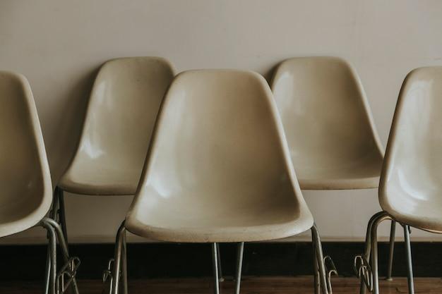 Cadeiras vazias brancas perto de uma parede branca