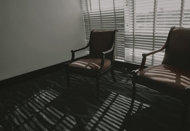 Cadeiras vazias com luz e sombra na sala. móveis para decoração em estilo vintage. duas cadeiras vazias na sala de estar, em pé no chão de carpete, perto das cortinas de plástico venezianas. cadeira de madeira.
